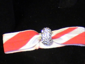 This Mair's Hair Tie is made with a Red and White Candy Cane Stripe with a Bead that shines like White Diamonds.  The hair tie can be used for long hair or any that can be pulled up into a Ponytail. It also lends itself to a wristband bracelet.